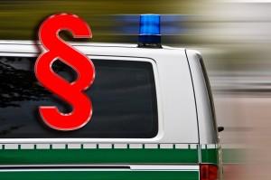 Polizeiauto mit Blaulicht und ein rotes Paragraphenzeichen