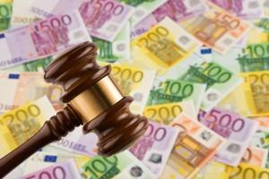 Gerichtshammer vor einem Hintergrund aus Euro Scheinen
